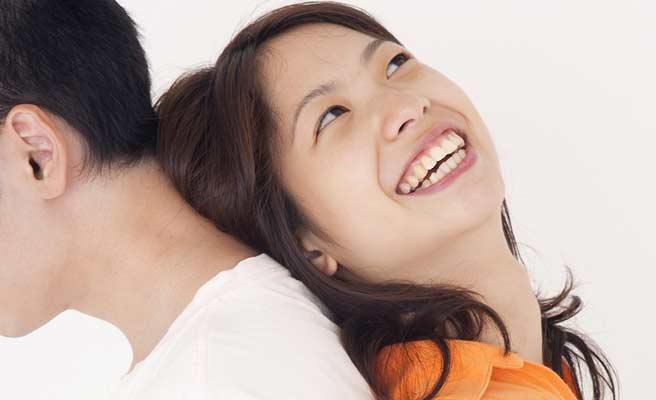 彼氏の背中によりかかり笑顔の女性