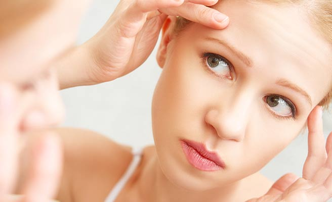 鏡に映る顔を見ながら肌の手入れをする女性