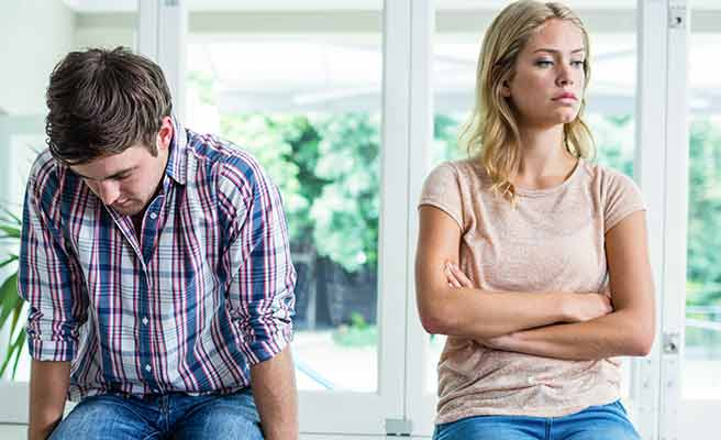 彼氏の隣で腕組みしてそっぽを向く女性