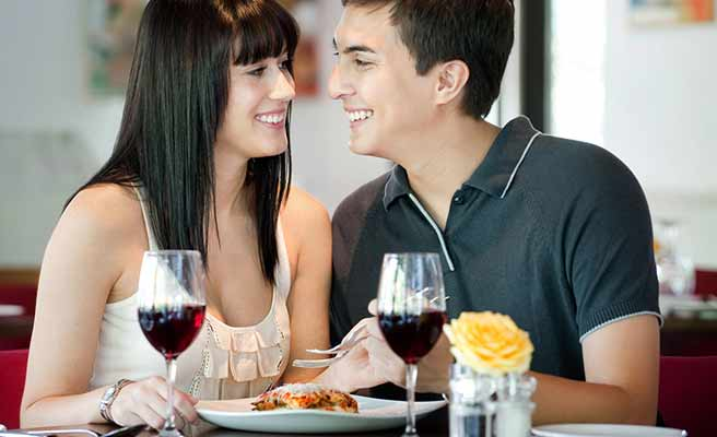 男と食事をしながら体を付ける女性