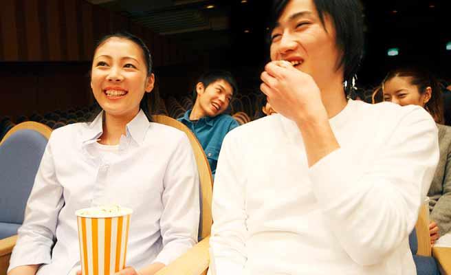映画館で恋人と並んで鑑賞する女性