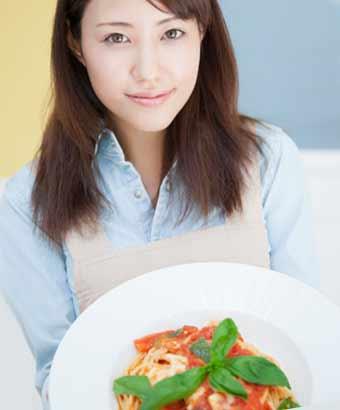 野菜を添えたパスタを持った女性