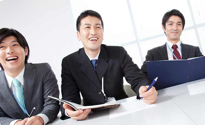 会議する会社員の中で笑顔を見せる男性