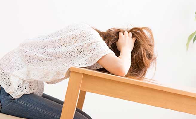 机に頭をつけて悩む女性
