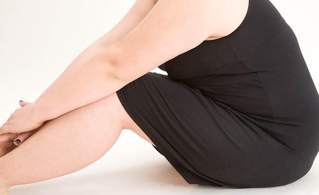 太った女性が膝を抱えて座る