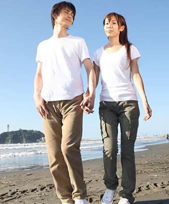 二人で手を繋いで浜辺を歩く