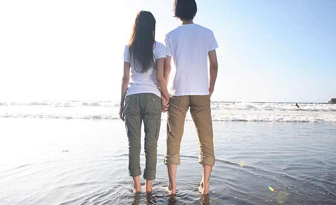 海辺で手を繋いで並び立つカップル