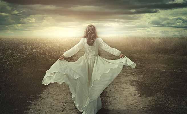 一人で道を歩むドレス姿の女性