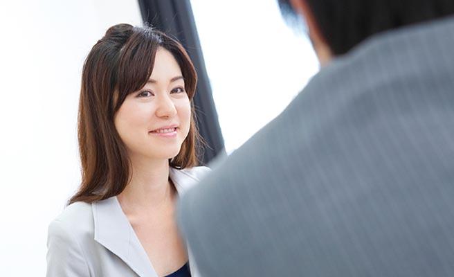 職場で男性と対面しながら微笑む女性