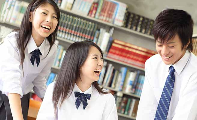 図書室で談笑する高校生の男女