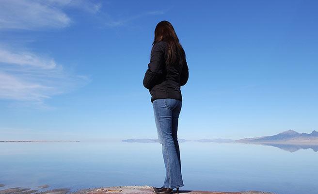 一人で広大な風景の前に佇む女性