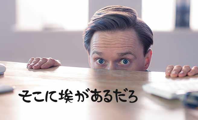 机の上の埃を指摘する男性