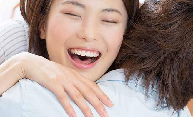 彼氏に抱きつく女性の笑顔