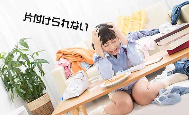 乱雑な部屋で頭を抱える女性