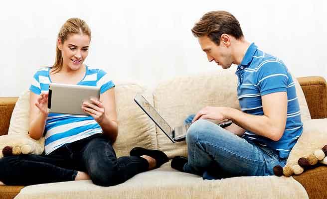 ソファの上で各々がパソコンを見ているカップル