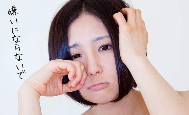 片手で涙を拭く動作する女性