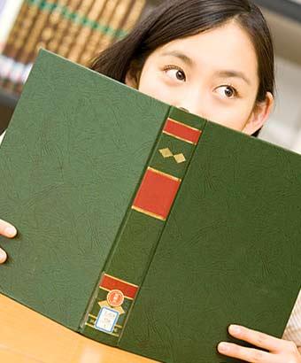 本を立てて顔を隠す女子大生