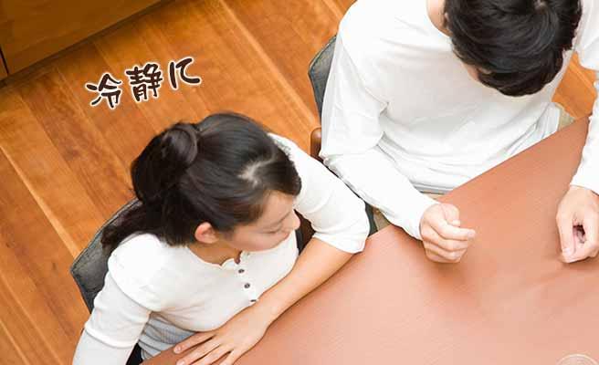 テーブルに横並びに座って話し合う夫婦