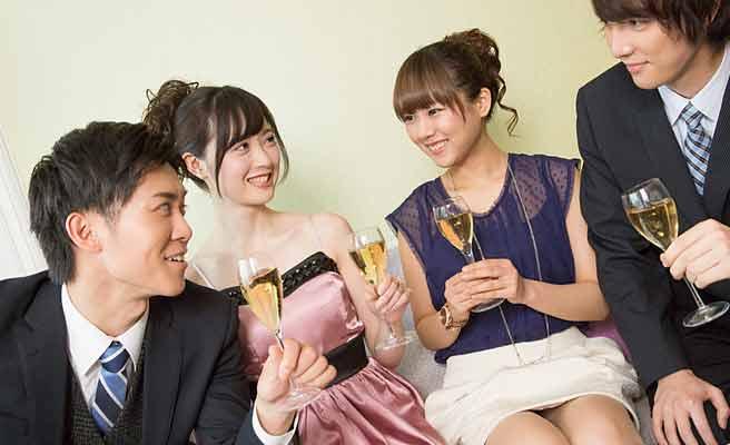 パーティで男女がグラスを持って談笑