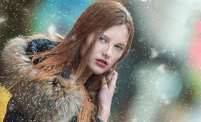 雪の中に立って振り返る女性