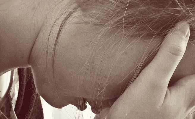 顔を手で覆いながら泣く女性