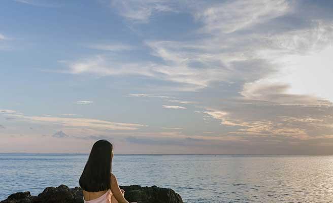 一人で海辺に座り水平線を見つめる女性