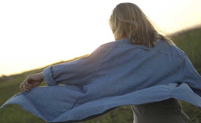 風にシャツを受けながら丘の上へ歩いていく女性