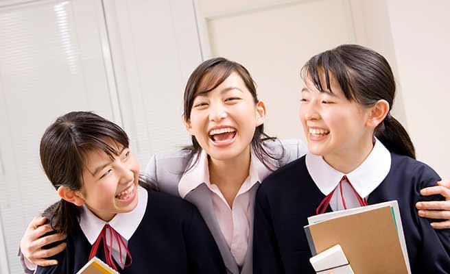 先生に肩を抱かれて笑う女生徒二人