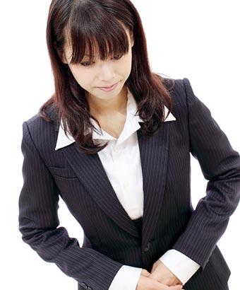 スーツ姿で頭を下げる女性