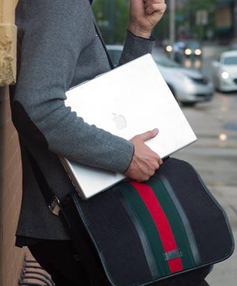 バッグとパソコンを持つ男性
