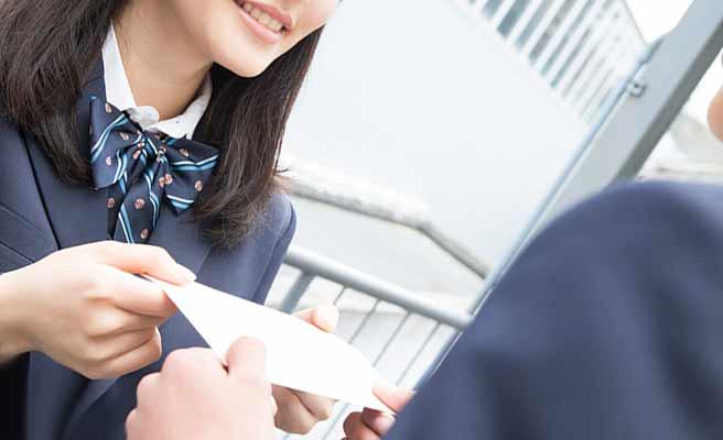 手紙を男子学生に差し出す制服の女子生徒