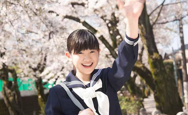 通学路で手を振る女子中学生