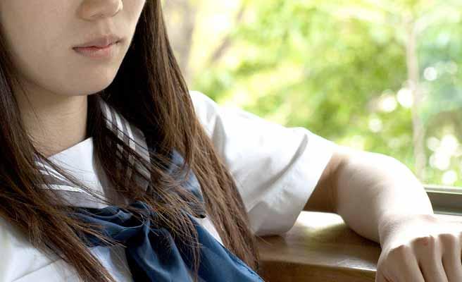 窓辺に寄りかかる女子中学生