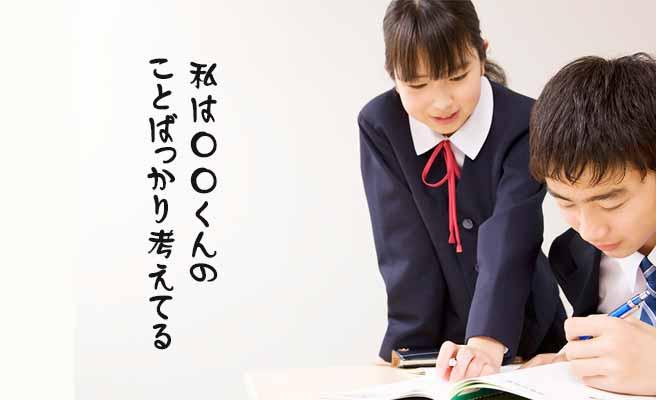男子生徒の傍に立って一緒にノートを見ている女子中学生