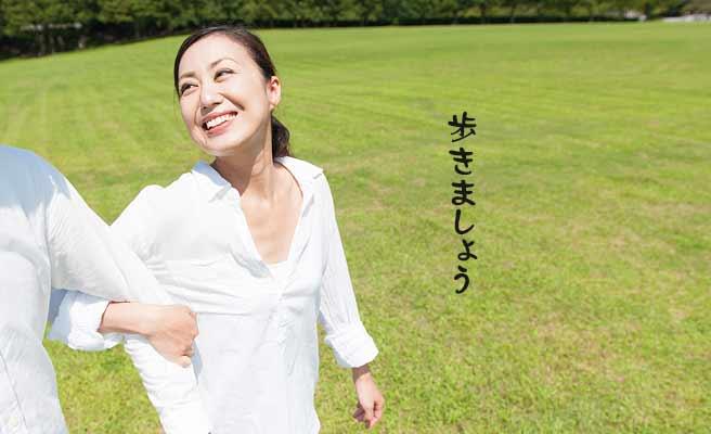 公園で彼氏の腕を取ってリードする女性