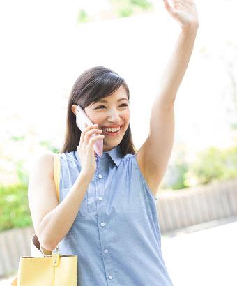手を上げて合図する笑顔の女性