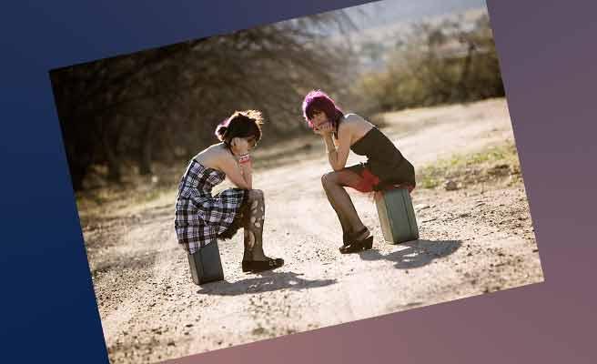 田舎道でスーツケースの上に腰かける女性二人