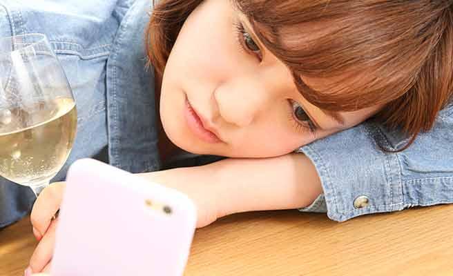 自分の腕枕でスマホを見つめる女性