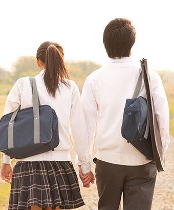 手を繋いで歩く高校生カップル