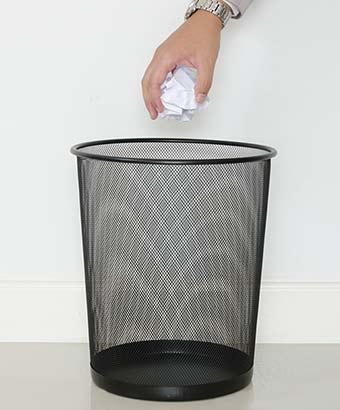 ごみ箱に紙屑を捨てる男性の手