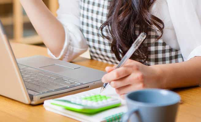 電卓とパソコンを置いてお金の計算をする女性