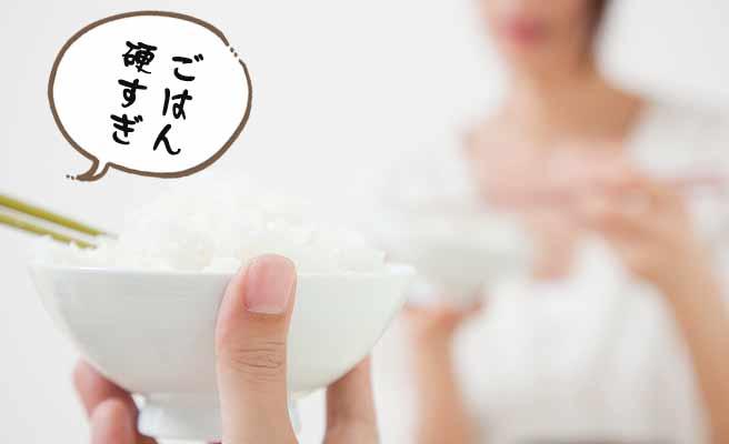 ごはん茶碗を持ちながら「ごはんが硬い」と妻に向かって言う夫
