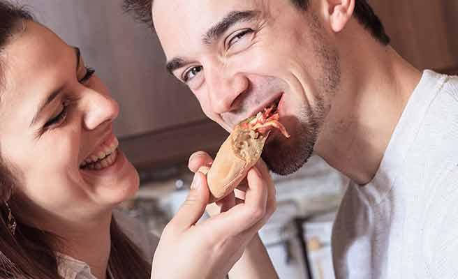 彼女が持つパンを咥える男性