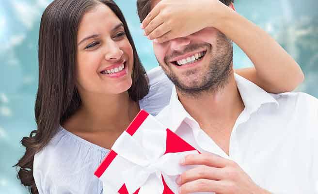 彼氏を手で目隠ししてプレゼントを渡す女性