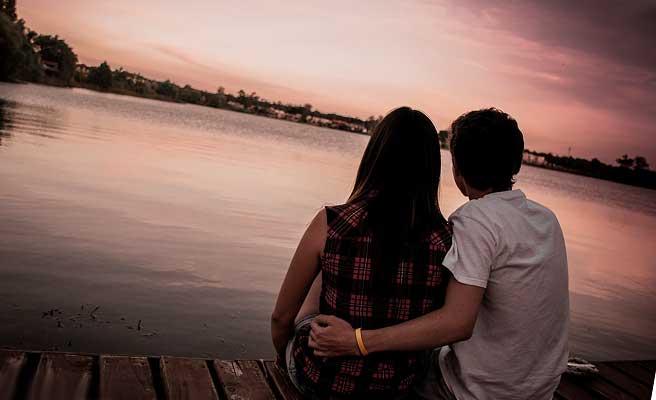 夕暮れ空を見つめるカップル