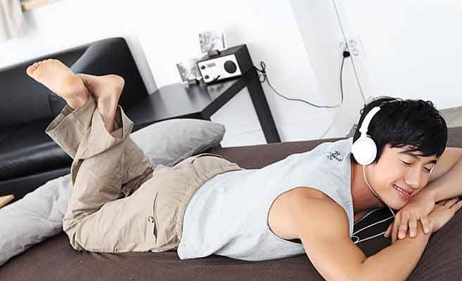 部屋で横になってヘッドホンで音楽を聴く男性