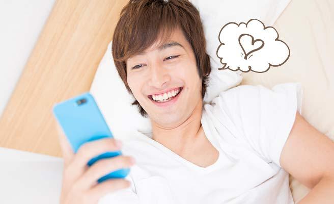 ベッドに横になったままスマホを見て笑う男性