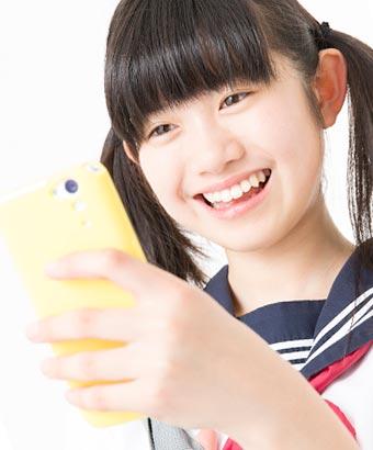 スマホを見て喜ぶ女子中学生