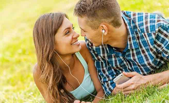 一緒にイヤホンを付けて音楽を聴きながら見つめ合うカップル