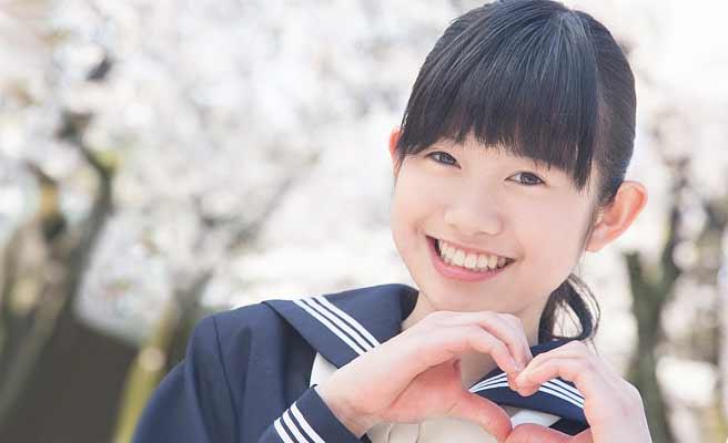 ハートマークを手で作る女子中学生
